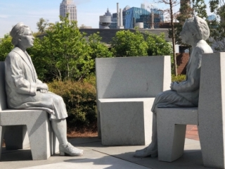 Figures of Rosa Parks at age 42 and age 92, seated on separate chairs facing eachother with an empty chair between them.