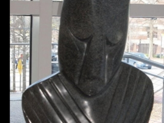 sculpted and polished black stone, a human face with eyes cast down and upper torso, no arms