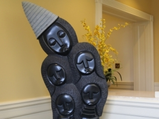 Five carved faces in smooth black finish with conical hat in gray textured finish. Hair surrounding faces is textured in a convex pattern as well