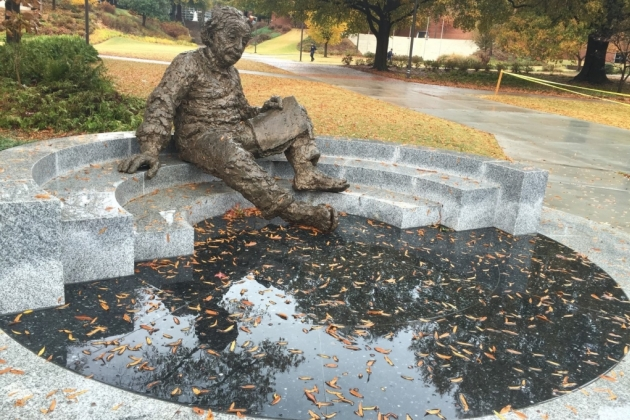Bronze figure of Albert Einstein seated on a semi circular bench, with a book on his lap, contemplating the map of the stars.